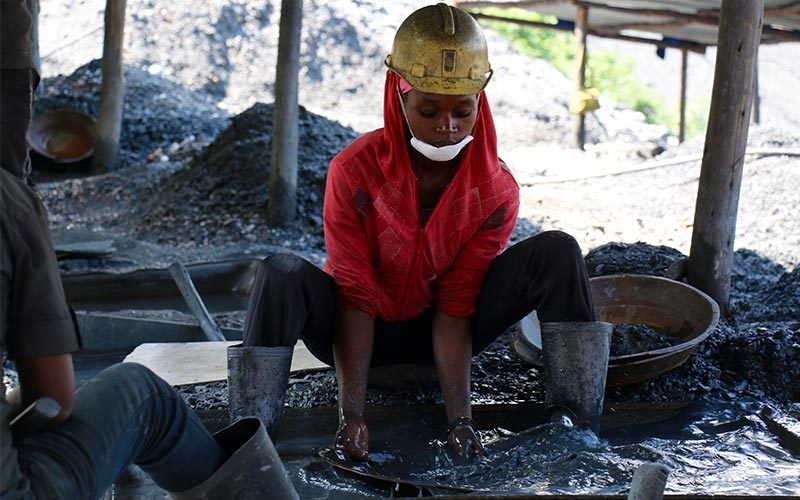 Female artisanal and small-scale miner panning for minerals wearing safety equipment.