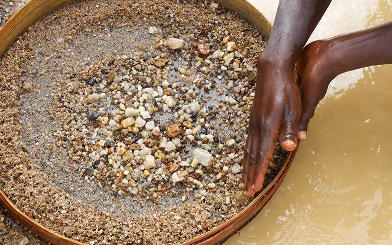 Female artisanal and small-scale miner panning for minerals.