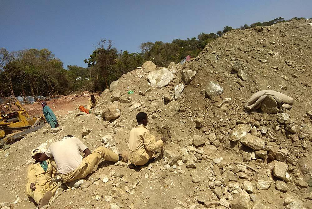 Sorting through waste pile at an emerald mine, Ethiopia.